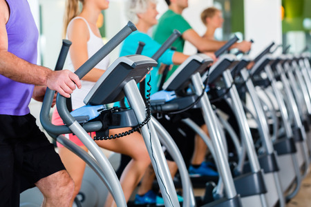 Group with senior and young men and women on elliptical treadmill trainer in fitness gym exercising