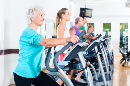 old ladies: Group with young and Senior women and men on elliptical trainer exercising in gym