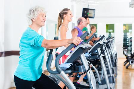 eliptica: Grupo con las mujeres y los hombres en bicicleta elíptica ejercitan en gimnasia jóvenes y mayores