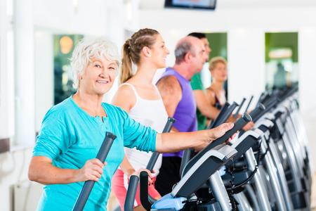 mujeres ancianas: Grupo con las mujeres y los hombres en bicicleta elíptica ejercitan en gimnasia jóvenes y mayores