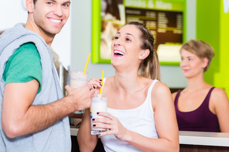 People drinking protein shakes in fitness gym bar Stock Photo