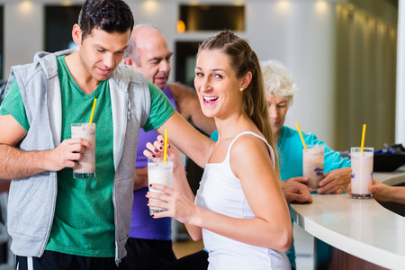 People drinking protein shakes in fitness gym bar Foto de archivo