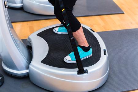 fitnes: Kobieta w siłowni płyty robi ćwiczenia fitness