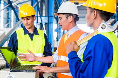 supervision: Personas de los trabajadores y el ingeniero en la fábrica en el entrenamiento de producción con el ordenador portátil