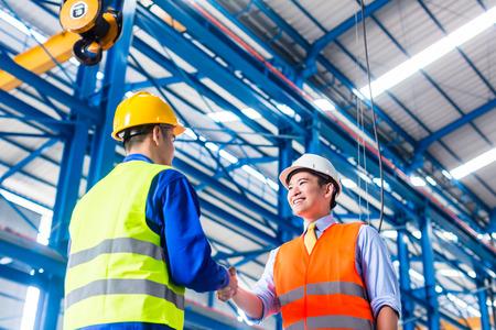 Werknemer en de klant die overeenkomst in de fabriek handen schudden