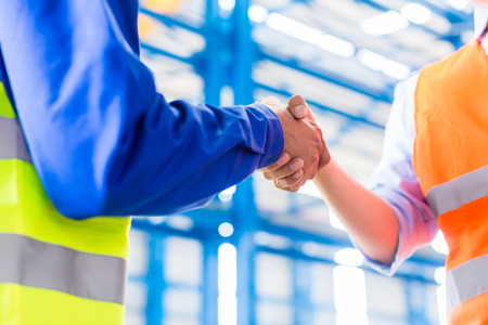 concluding: Worker and engineer having handshake in factory concluding agreement Stock Photo