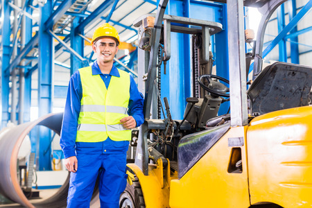 Forklift driver standing proud in manufacturing plant Banque d'images