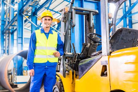 carretillas almacen: Conductor del montacargas se coloca orgulloso en la planta de fabricación