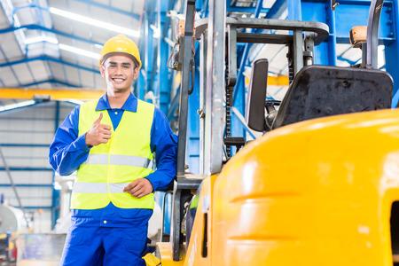 warehouse forklift: Conductor del montacargas se coloca orgulloso en la planta de fabricaci�n