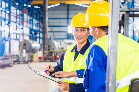 ouvrier: Ouvrier et conducteur de chariot élévateur dans l'usine industrielle regardant la caméra