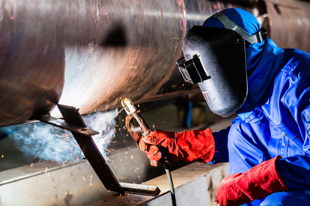 Welder in factory welding metal pipes Stock Photo
