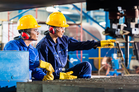 Werknemer in Aziatische fabriek op industriële metalen snijbrander machine Stockfoto - 37846869