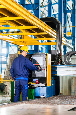 control panel: Trabajador en la planta de fabricaci�n en el panel de control de la m�quina CNC