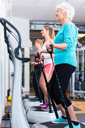 Group on vibrating plates in gym training for fitness sport Standard-Bild