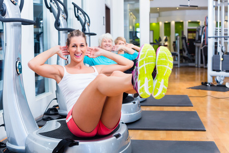 Group of senior and young people on vibrating plates in gym training abs for fitness sport Stock Photo