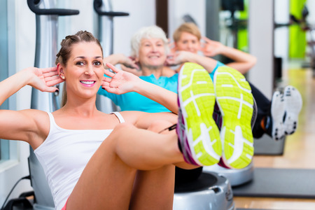situp: Group of senior and young people on vibrating plates in gym training abs for fitness sport Stock Photo