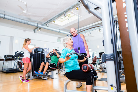 Senior woman doing back training with trainer in gym at machine photo