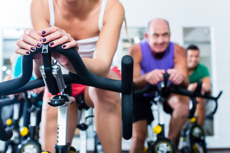 stationary bike: Group Senior and young people in spinning course on fitness bike in gym doing endurance and cardio training, the instructor is leading them on