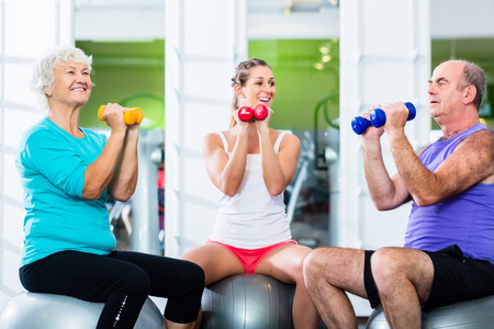Senior man and women with fitness trainer in gym lifting barbells as sport exercise photo