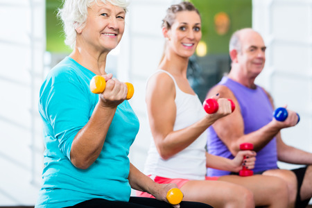 seniors: Senior man and women with fitness trainer in gym lifting barbells as sport exercise Stock Photo