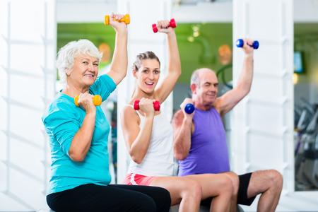 年配の男性と女性のスポーツ運動、バーベルを持ち上げるジムでフィットネス トレーナー