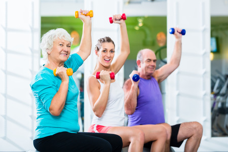 old people group: Senior man and women with fitness trainer in gym lifting barbells as sport exercise Stock Photo