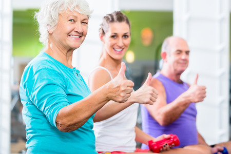 thể dục: Người đàn ông và phụ nữ với huấn luyện viên thể dục tại phòng tập thể dục nâng barbells như tập thể dục thể thao cao cấp