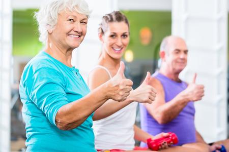 fitnes: Starszy mężczyzna i kobieta z trenerem fitness w siłowni podnoszenia sztangi jak sportowe ćwiczenia