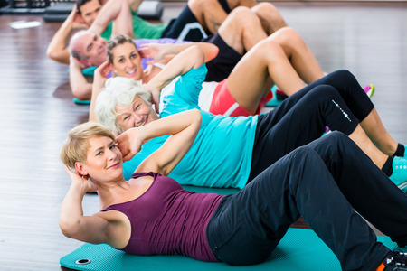 Group of senior people and young woman and men in fitness gym doing sit-ups on the floor Banco de Imagens