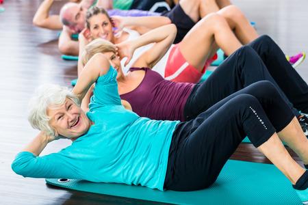 tercera edad: Grupo de gente mayor y joven mujer y el hombre en el gimnasio de fitness haciendo abdominales en el suelo
