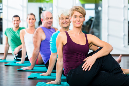 situp: Group of senior people and young woman and men in fitness gym doing sit-ups on the floor Stock Photo