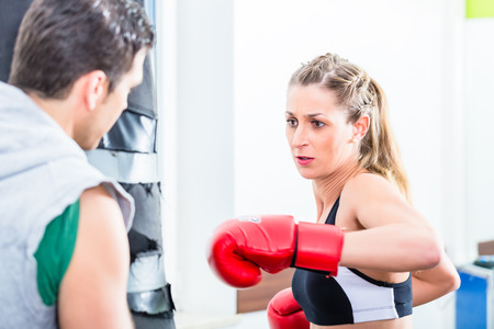 sandbag: Young woman with trainer in boxing sparring hitting sandbag Stock Photo