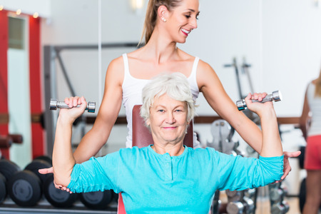 Senior women with fitness trainer in gym lifting dumbbell for pectoral training as sport exercise