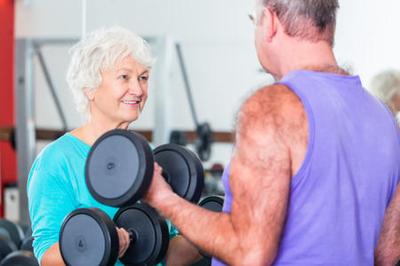senior fitness: senior couple, man and woman, in gym lifting dumbbells in fitness exercise workout