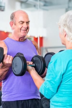 senior couple, man and woman, in gym lifting dumbbells in fitness exercise workout photo