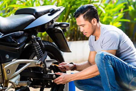 motorcycles: Asian man doing motorcycle maintenance in his garden Stock Photo
