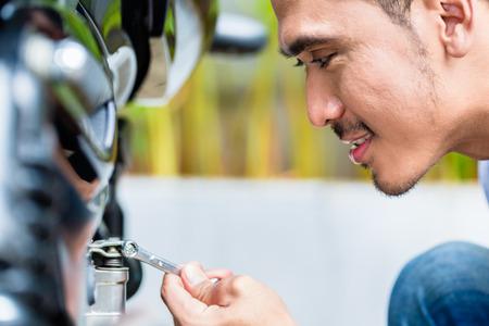 maintaining: Close up of Asian man maintaining motorcycle