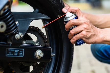 in chains: Hombre engrasar la cadena de la motocicleta, close up por lado Foto de archivo