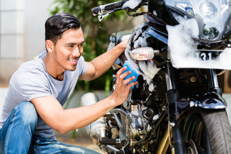 motor bike: Asian man washing his motorcycle or scooter with soap and sponge Stock Photo