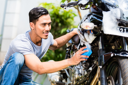 Asian man washing his motorcycle or scooter with soap and sponge Stock Photo