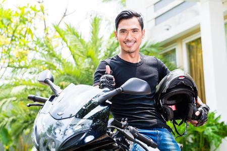 motociclista: Hombre joven asiático y su moto o scooter