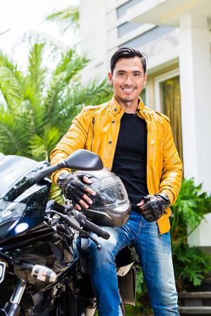 casco moto: Hombre joven asiático y su moto o scooter