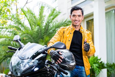 casco moto: Hombre joven asi�tico y su moto o scooter