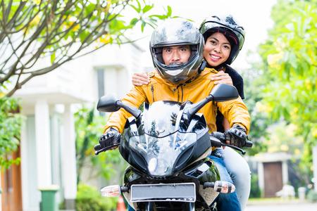 オートバイの乗馬のヘルメットとカップル、妻は夫の後ろに座っています。