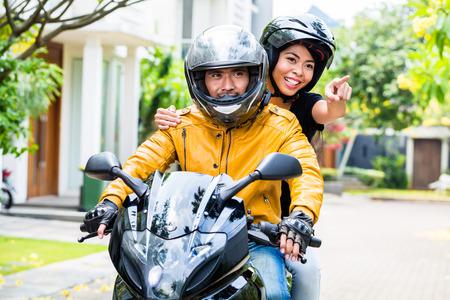 Pár s přilby na koni motocyklu, manželka sedí za svým manželem