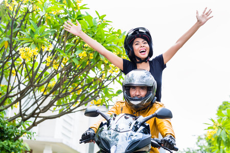arms out: Indonesian woman feeling free on motorcycle stretching her arms out