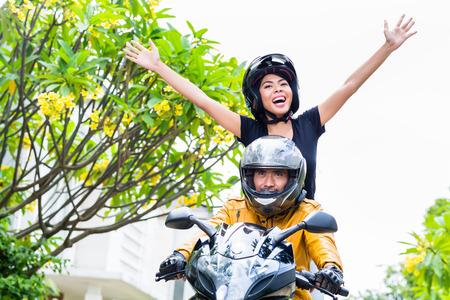 casco moto: Mujer indonesia sentirse libre en la motocicleta que estira sus brazos hacia fuera