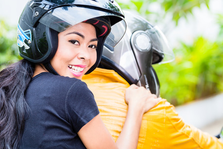 Asian couple riding motorcycle, wife is sitting behind her husband