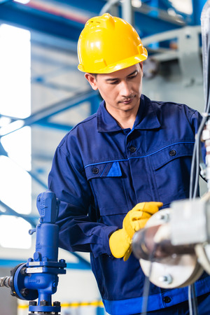 Technician in Asian factory at machine maintenance working with wrench Stock Photo