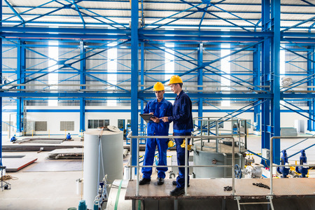 Two workers in large metal workshop or factory checking work standing on large machine